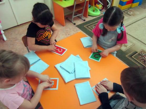 Дети сидят за столом, перед ними карточки с цифрами и листы картона