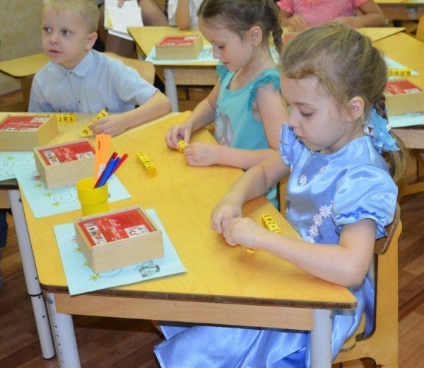 Дети сидят за столиком в детском саду, перед ними математические игрушки