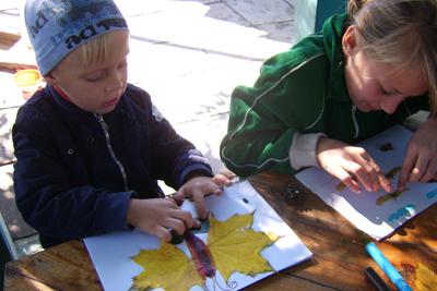 Дети делают аппликацию из листьев