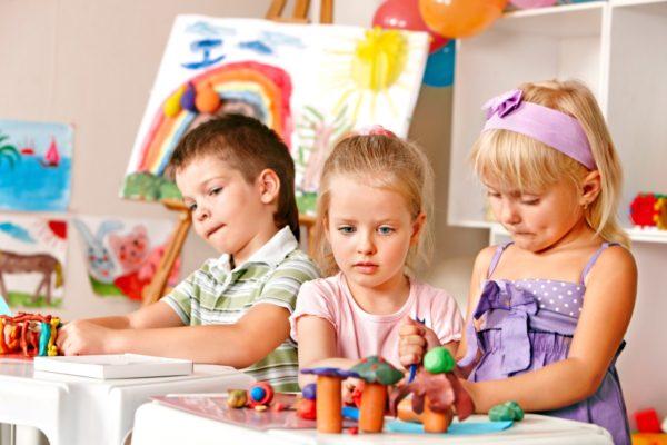 Две девочки и мальчик лепят из пластилина