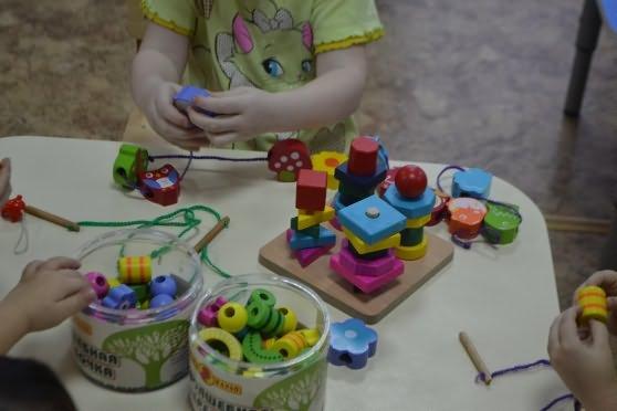 Дети нанизывают детали деревянной мозаики на шнурок