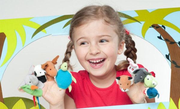 Девочка с пальчиковыми куклами радостно улыбается