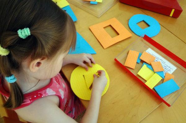 Ребёнок вставляет треугольник в треугольное отверстие в круге