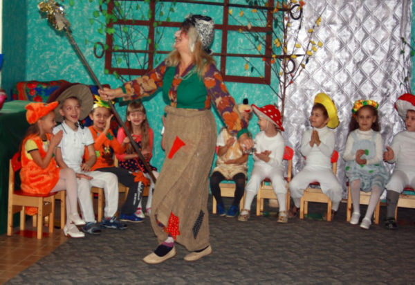 Воспитательница в костюме Бабы-Яги среди детей, одетых в костюмы лесных зверей и грибочков