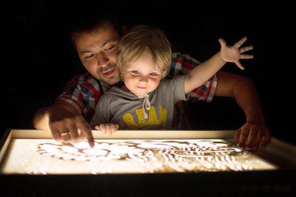 Мальчик с папой рисуют по песку