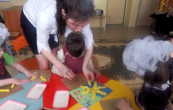 Коррекционное занятие (ребёнок лепит на плоскости)