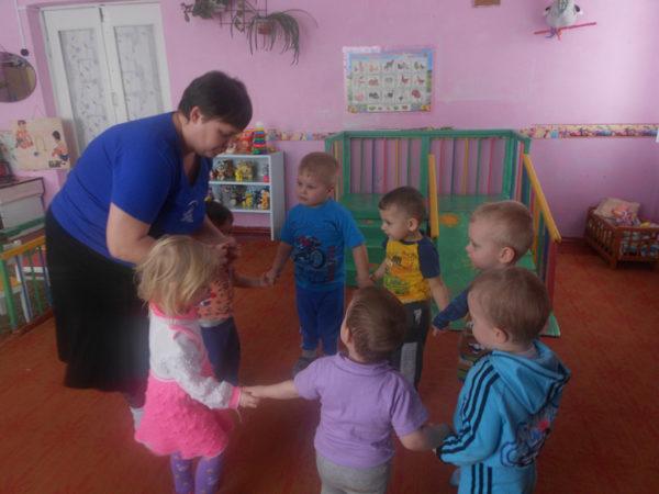 Малыши стоят рядом с воспитателем