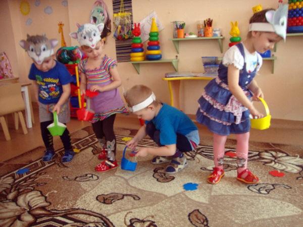 Дети в масках животных собирают игрушечные цветы в корзинки