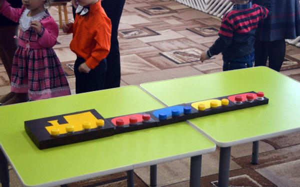 Поезд-конструктор с разноцветными вагонами на столе
