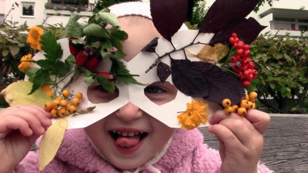 Малыш в маске, украшенной веточками рябины