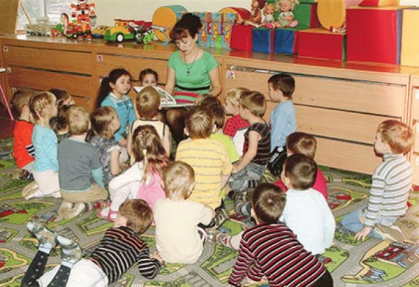 Воспитатель читает детям книжку