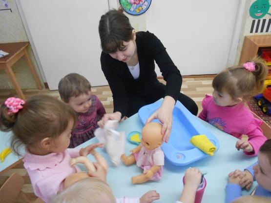 Воспитательница показывает, как мыть и вытирать куклу