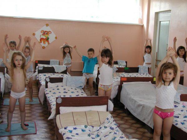 Дети стоят с поднятыми руками у кроватей