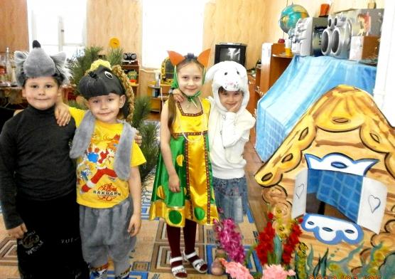 Дети в костюмах стоят на фоне декораций