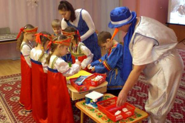 Педагоги и дети в сказочных костюмах собирают конструктор