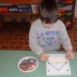 Мальчик выложил домик на дощечке с кнопками