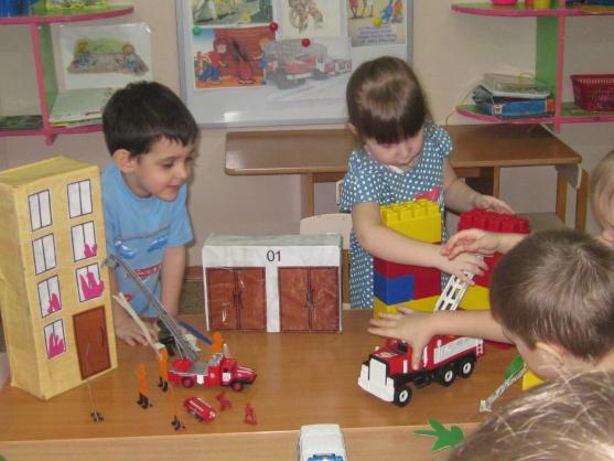 Дошкольники разыгрывают с помощью игрушек сцену тушения пожара