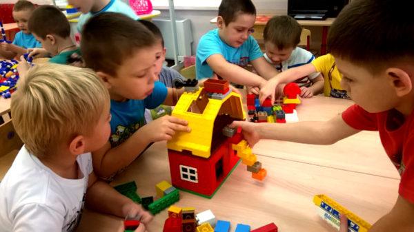 Дети, разбившись на группы, собирают конструктор