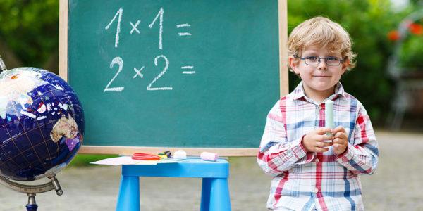 Мальчик стоит у доски с математическими примерами
