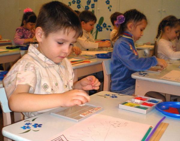 Ребёнок смотрит на лист бумаги, где размещены точки с линиями