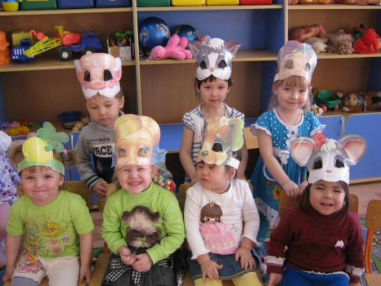Семеро малышей сидят с масками на головах и смеются