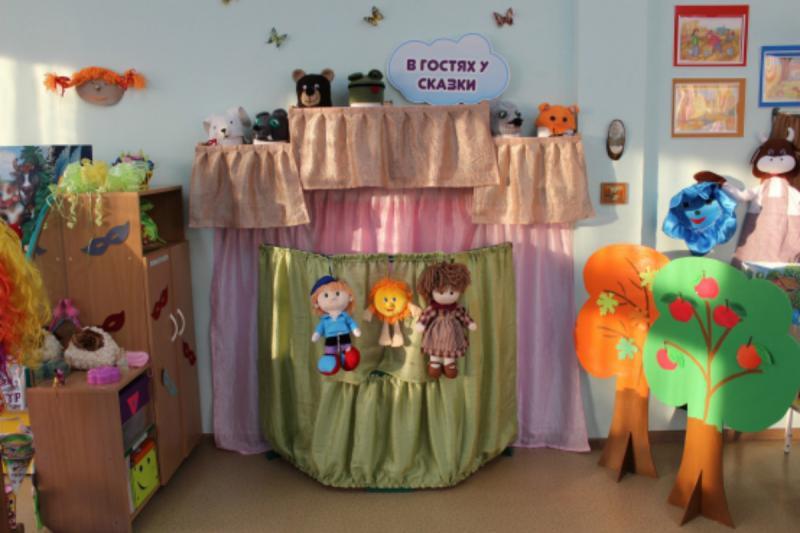 Театральный уголок: ширма, деревья и шкаф с игрушками, стоящий боком