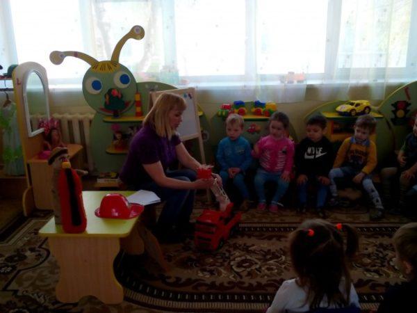 Воспитатель демонстрирует малышам пожарную машину и атрибуты пожарного