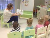 Воспитательница показывает детям, сидящим на стульях, картинку в книжке