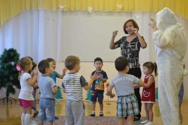 Воспитательница с детьми делает физкультминутку