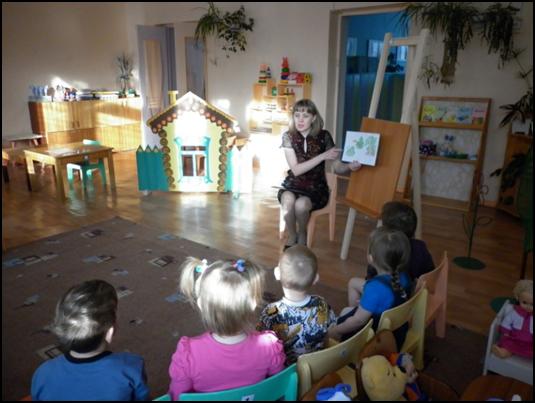 Воспитательница в тёмном коротком платье показывает детям картинки в книжке