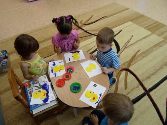 Четверо детей за овальным столиком делают аппликацию — уточку
