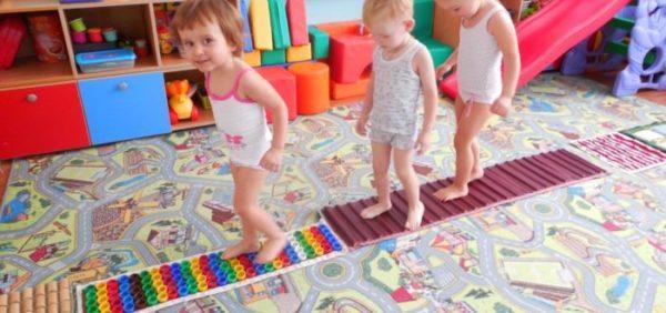 Дети идут по разноцветным массажным коврикам