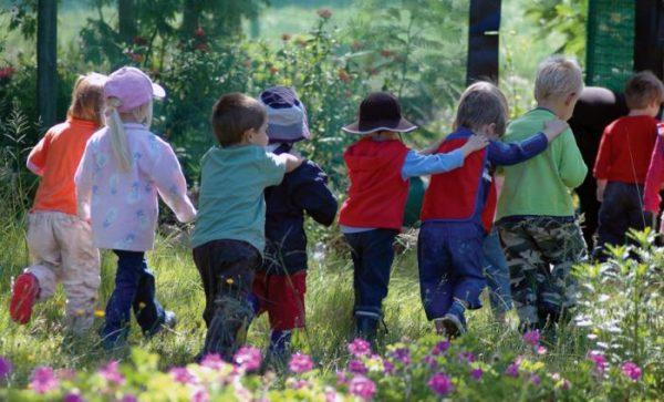 Дети идут строем по траве, руки на плечах друг друга