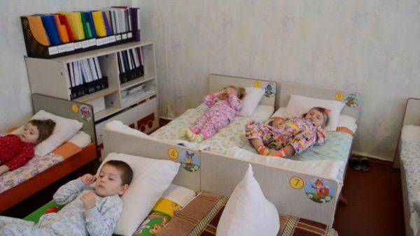 Дети лежат в кроватках в спальне, слева шкаф с папками