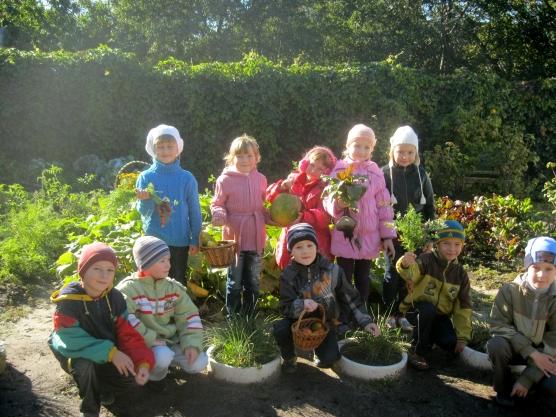 Дети на территории детского сада, одеты по-весеннему