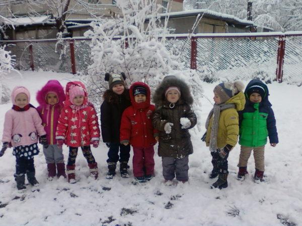 Дети на зимней прогулке стоят около забора
