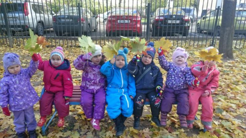 Дети с осенними листьями в руках сидят на лавочке