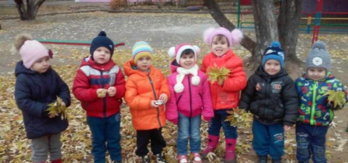 Дети стоят с осенними листьями в руках
