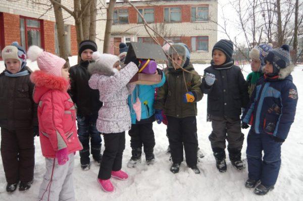 Дети стоят вокруг кормушки, девочка насыпает туда корм