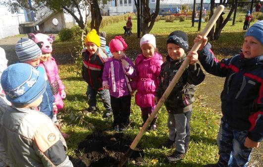 Дети стоят вокруг небольшой ямы, один мальчик держит лопату