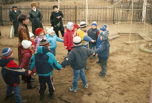 Дети в куртках и шапках стоят во дворе, взявшись за руки
