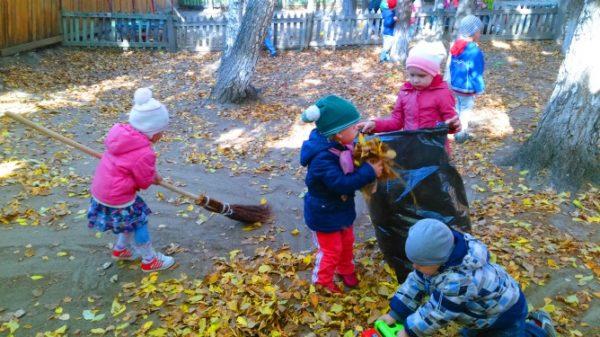 Дети убирают листья на участке