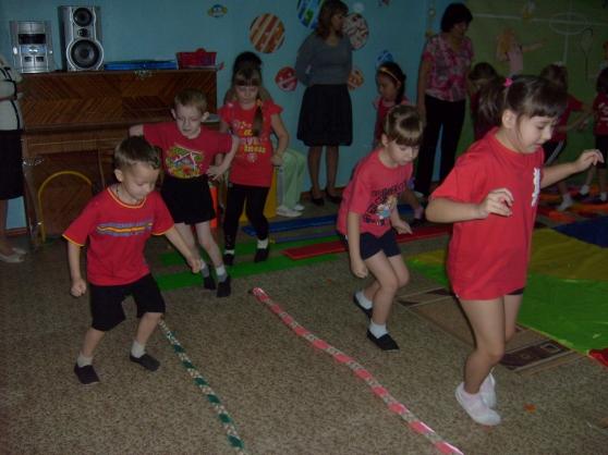 Дети в красных футболках идут вдоль разложенных на полу канатов
