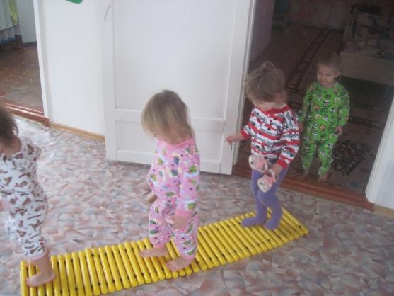 Дети в пижамах идут по массажному коврику-