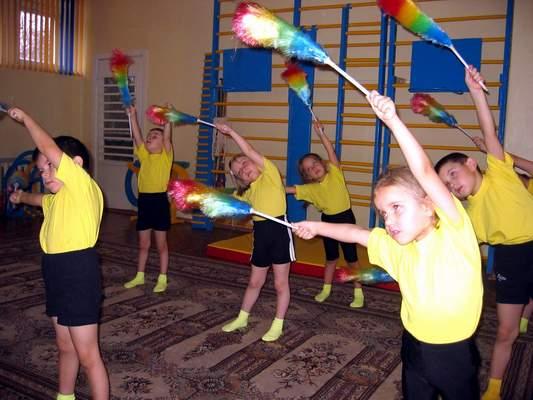 Дети в жёлтых футболках делают наклоны с султанчиками