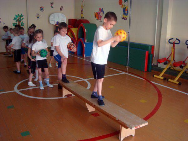 Дети ведут мяч по скамье