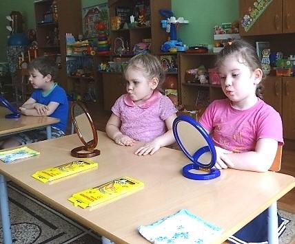 Дети выполняют артикуляционную гимнастику перед зеркалами