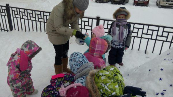 Дети и воспитатель в зимней одежде рассматривают снег