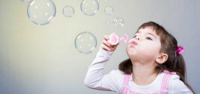 Девочка дует мыльные пузыри