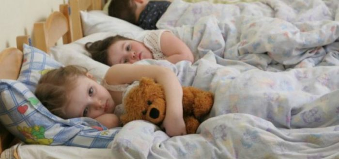 Девочка с мишкой лежит в кровати в детском саду